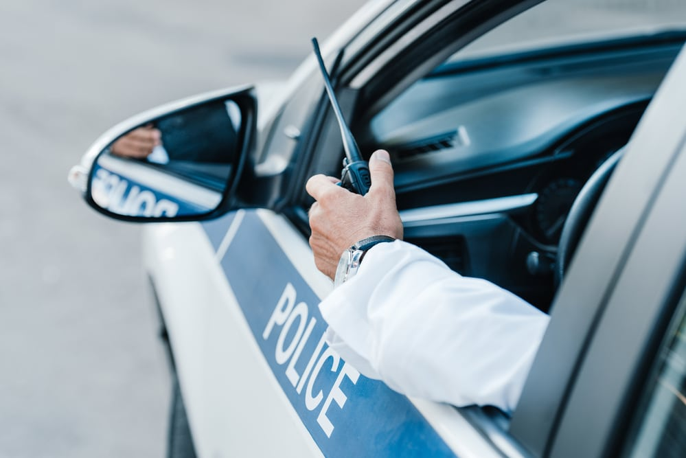 Close-up of police car window, arm hanging out with walkie talkie