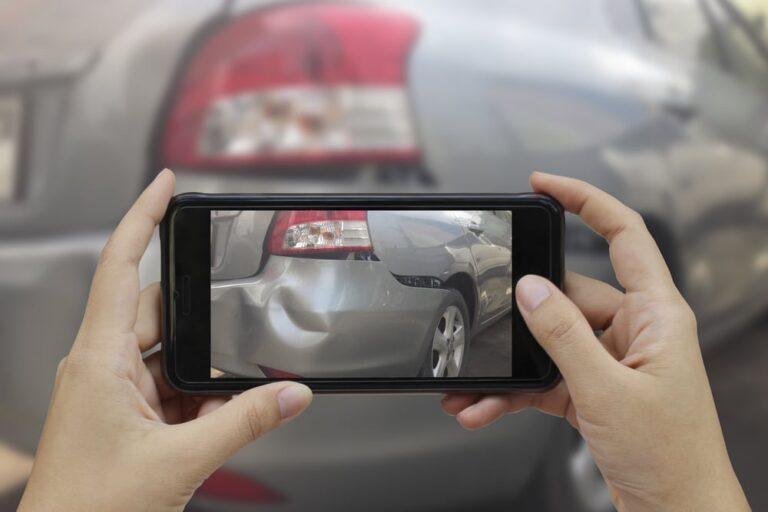 Close-up of someone taking a picture of a car accident damage with their phone