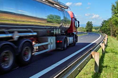 Mirroring the landscape chrome tank truck moving on a highway