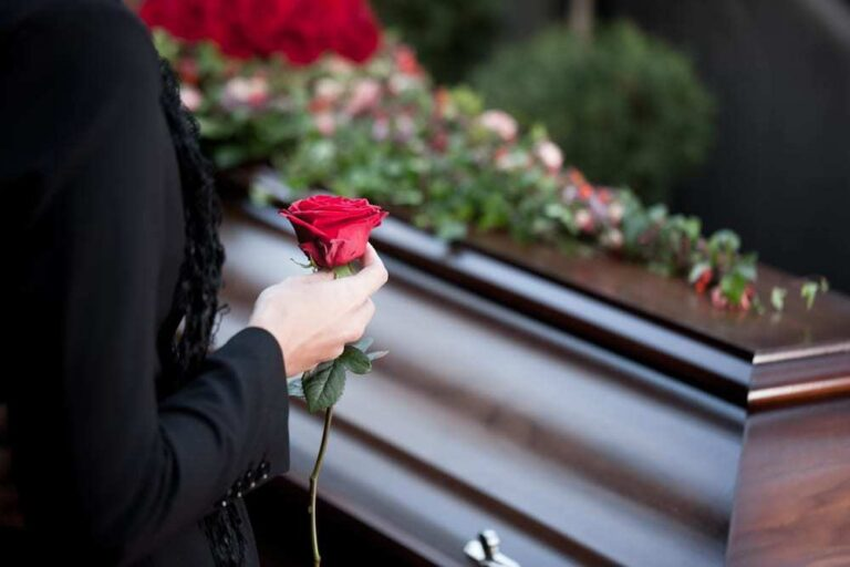 Woman holding a rose at a funeral