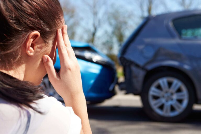 Stressed Young Woman Looking at Car Accident
