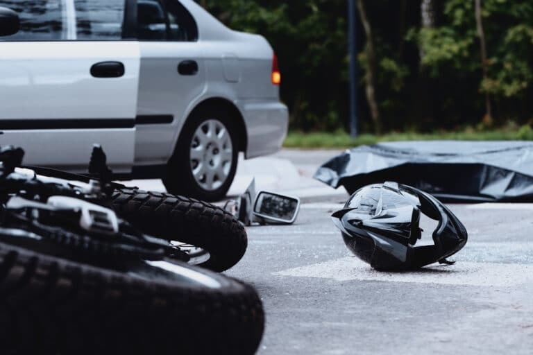 Motorcycle and helmet on street after crash, car in background