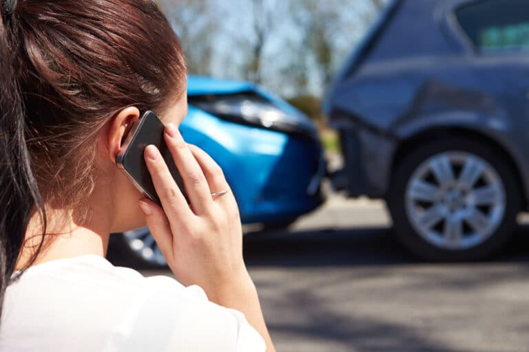 Close-up of young woman friend behind, talking on phone, car crash in background