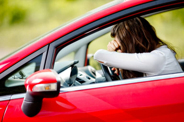Young woman sitting in car, upset