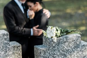 Flowers on tombstone, man comforting woman in background